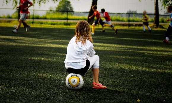 Nena mirant un partit de futbol asseguda sobre una pilota - Flickr - CC BY-ND 2.0
