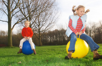 Nenes saltant sobre pilotes gegants