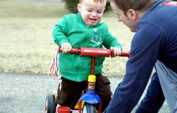 Nen aprenent a pedalejar en tricicle amb el seu pare - Stacy Brunner - Flickr - CC BY-NC-SA 2.0