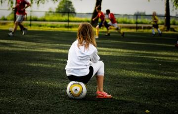 Niña mirando un partido de futbol sentada encima de un balón - TJook - Flickr - CC BY ND-2.0