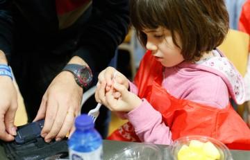 Niña pinchándose el dedo para un control glucémico - Hospital Sant Joan de Déu