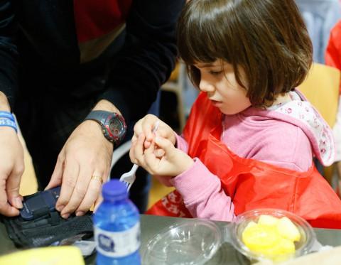 Nena punxant-se el dit per fer-se un control glucèmic abans d'esmorzar - Hospital Sant Joan de Déu