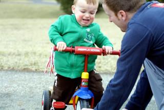 Niño aprendiendo a pedalear un triciclo con su padre - Stacy Brunner - Flickr - CC BY-NC-SA 2.0