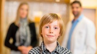 Niño seguro de sí mismo, con su madre y un médico