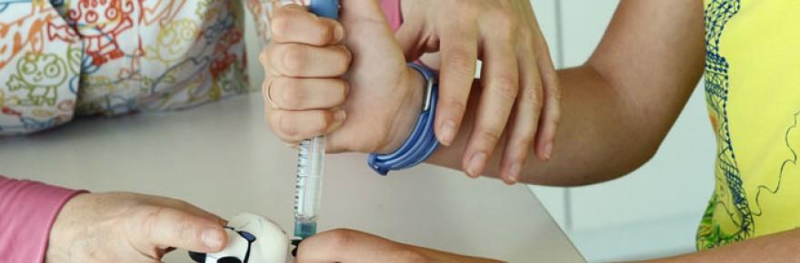 Educadora del Hospital Sant Joan de Déu enseñando a un niña cómo inyectar la insulina