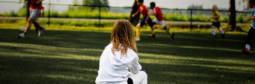 Niña mirando un partido de fútbol sentada sobre una pelota - Flickr - CC BY-ND 2.0